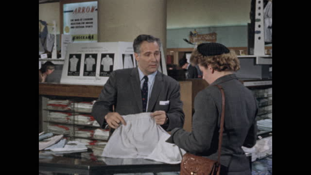 department store salesman promotes men's briefs with elastic waistband to woman - salesman stock videos & royalty-free footage