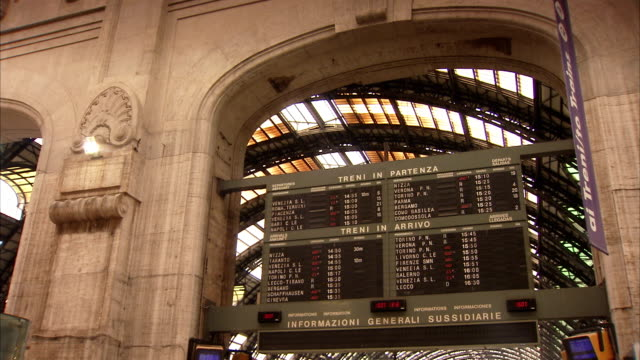 a departure board fills an archway inside milano centrale railway station. available in hd. - stazione video stock e b–roll