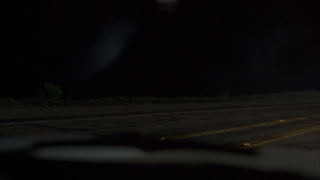 A POV depicts a car driving on a dark road and swerving to miss an oncoming car.