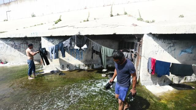 deportees wash clothes just across the border on april 6 2018 in tijuana mexico - zoll und einwanderungskontrolle stock-videos und b-roll-filmmaterial