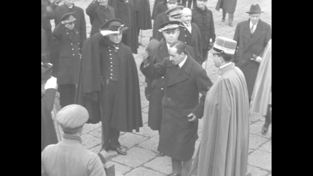 Deposed Spanish king Alfonso XIII and Italy's Crown Prince Umberto get out of car at Naples dock Alfonso shakes hands with man who salutes Prince...