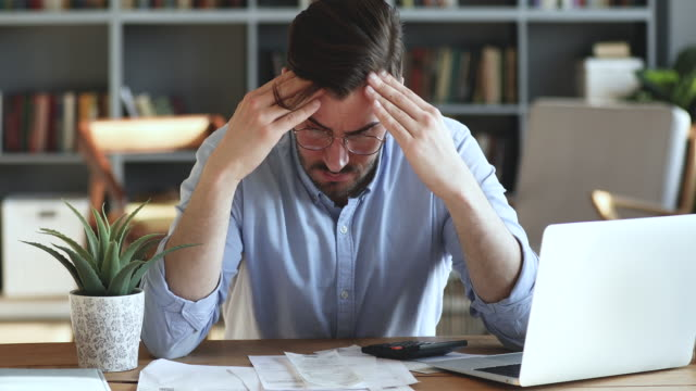 Depressed man feeling worried about financial problem doing paperwork