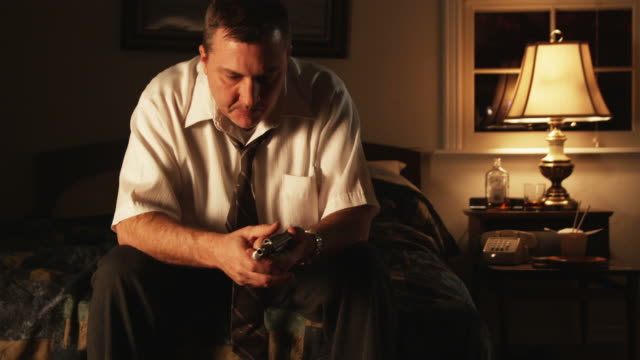 depressed man sitting and holding a handgun to his head - handgun stock videos and b-roll footage