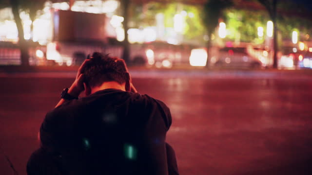 depressed man sitting on the street alone at dusk. - suicide stock videos & royalty-free footage