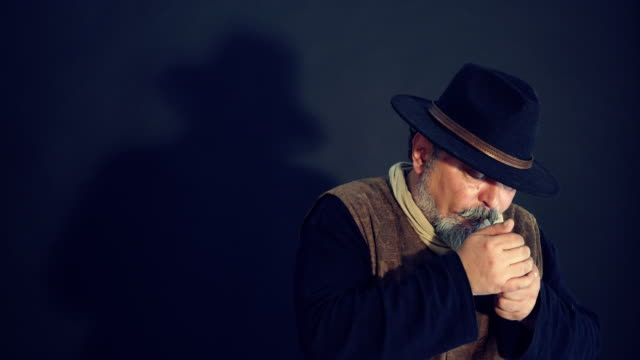 depressed man smoking cigar against black background - ozgurdonmaz stock videos and b-roll footage