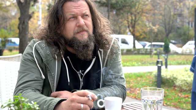 Depressed man smoking cigarette at the street café
