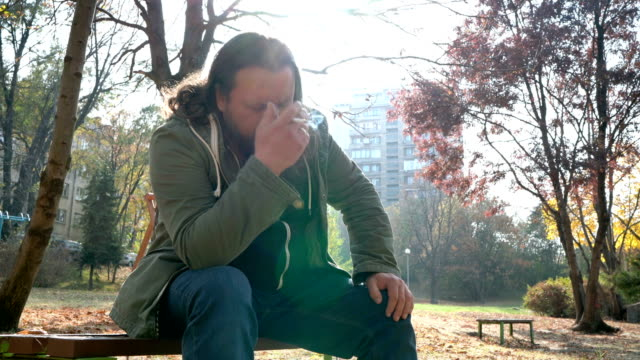 depressed man smoking cigarette in the park - restlessness stock videos and b-roll footage