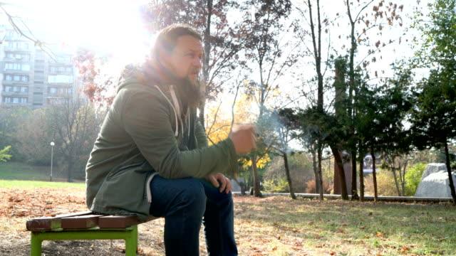 Depressed man smoking cigarette in the park