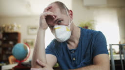 Depressed man wearing anti virus mask staying at home