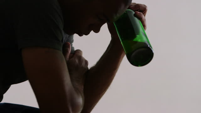 depressed man with liquor bottle - alcohol abuse stock videos & royalty-free footage