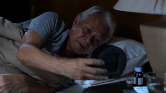 a depressed senior man lying in bed cannot sleep from insomnia - sad old asian man stock videos & royalty-free footage
