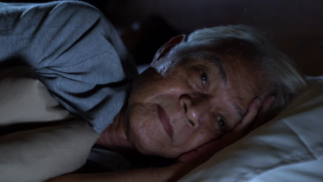 a depressed senior man lying in bed cannot sleep from insomnia - bedroom stock videos & royalty-free footage