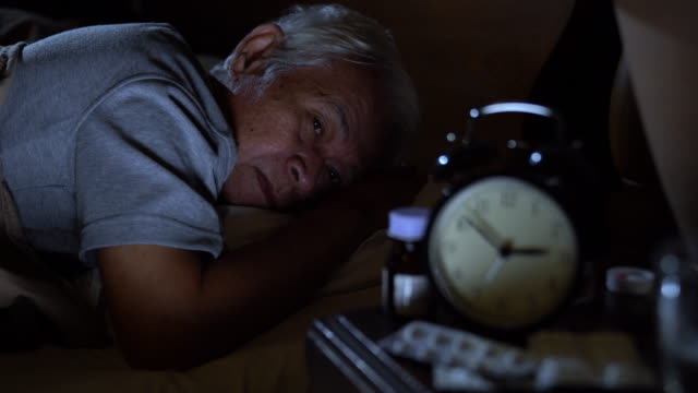 a depressed senior man lying in bed cannot sleep from insomnia - distressed stock videos & royalty-free footage