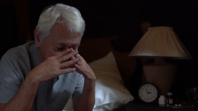 depressed senior person sitting in bed cannot sleep from insomnia - sad old asian man stock videos & royalty-free footage