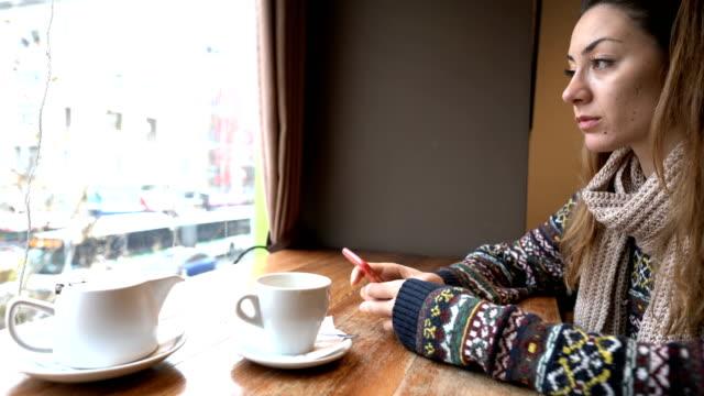 vídeos y material grabado en eventos de stock de mujer deprimida en la cafetería de mensajería en línea - incertidumbre