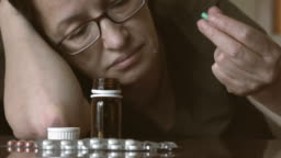Depressed woman beside a lot of pills