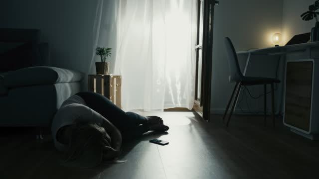 vidéos et rushes de femme déprimé de ds pleurant tout en se trouvant sur le plancher - se tenir la tête entre les mains