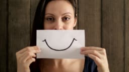 Depressed woman showing a smiley face painted on paper