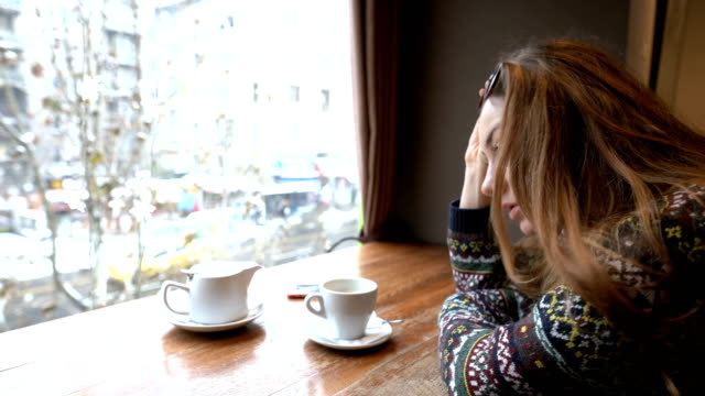 depressed woman sitting alone at the café - mid adult women stock videos & royalty-free footage