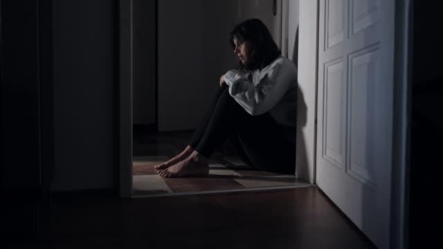 depressed woman sitting in corridor and crying at home. - violence stock videos & royalty-free footage