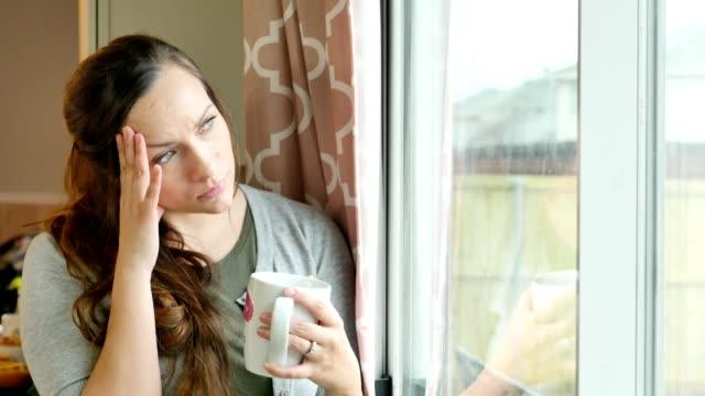 vídeos de stock, filmes e b-roll de mulher jovem deprimida parado na janela em sua casa - emoção negativa
