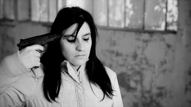 vidéos et rushes de femme dépressive qui tente de se suicider avec une arme à feu visant sur sa tête - hôpital psychiatrique