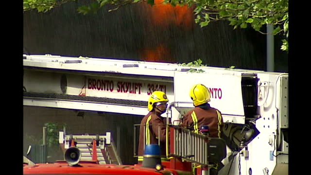 deptford warehouse fire; day smoke rising firefighters at scene smoke rising around houses firefighters on crane spraying blaze with water from hose - warehouse点の映像素材/bロール