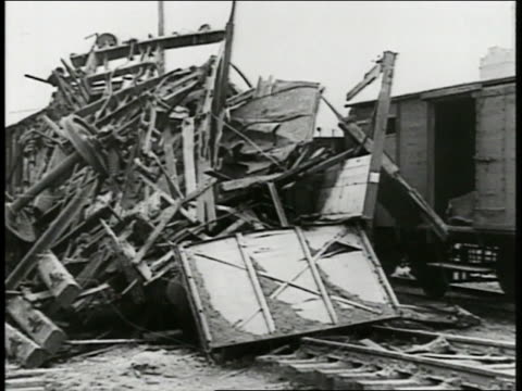 derailed bombed railroad train. wreckage of train cars. bomb destruction at airport , airplanes & biplanes destroyed, wreckage, destruction. - 1939 stock-videos und b-roll-filmmaterial