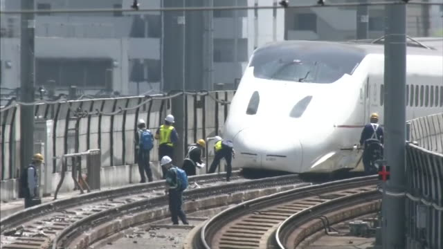 derailed kyushushinkansen bullet train and track workers seen in the shimmering heat track workers working on derailment recovery during 2016... - kyushu shinkansen stock videos and b-roll footage