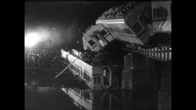 derailed train carriages sit on top of each other reflected by river / cu of man walking through destroyed carriage / serious crowd watches night... - 1967年点の映像素材/bロール