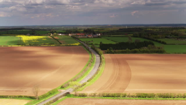 derbyshire farmland with country road - drone shot - plowed field stock videos & royalty-free footage