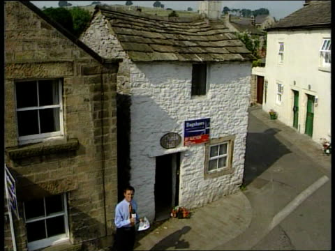 stockvideo's en b-roll-footage met very small house for sale england derbyshire youlgrave village street pan to i/c as along to tiny house la gv house with 'auction' notice on front... - derbyshire