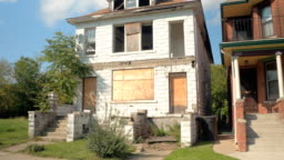 CLOSE UP Derelict decaying home next to beautiful semi-detached house in Detroit