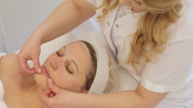 dermatologist applying face moisturizing mask on adult woman's face - beauty treatment stock videos and b-roll footage