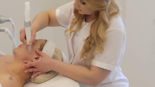 vídeos de stock, filmes e b-roll de dermatologista, dando um tratamento de microdermoabrasão para uma mulher adulta - dermatologia