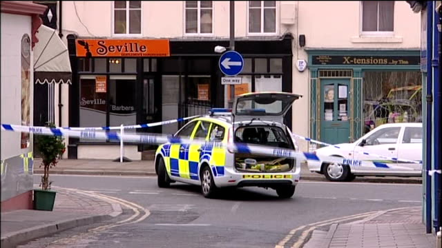 inquest 2nd june 2010 exact location unknown ext police car parked in cordonned area of road close shot of police officer with hand raised and sot... - derrick bird cumbria stock-videos und b-roll-filmmaterial