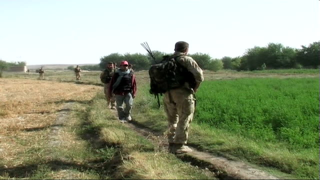 des browne defends afghanistan troop deployment; date unknown afghanistan: helmand province: ext british troops along through contryside on patrol - helmand stock videos & royalty-free footage
