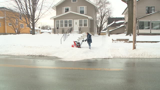 vídeos de stock e filmes b-roll de des moines, ia, u.s. - people use snowblowers and shovels to remove deep snow from sidewalks after heavy snowfall on tuesday, january 26. 2021. a... - pá para neve