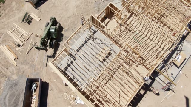 descending aerial drone shot of a group of construction workers framing a house on a sunny day - carpentry stock videos & royalty-free footage