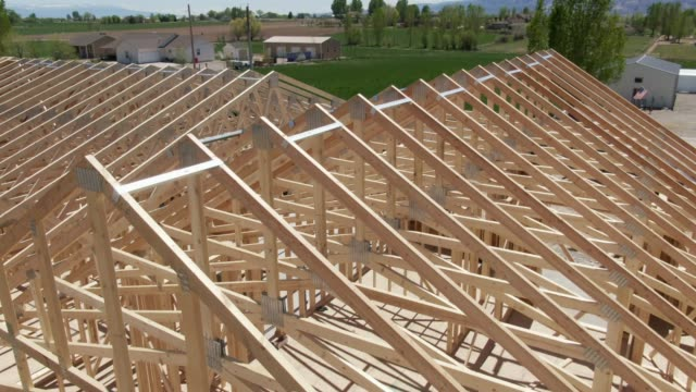 descending aerial drone shot of a row of wooden roof trusses of a framed house on a construction site with construction workers on a sunny day - costruire video stock e b–roll