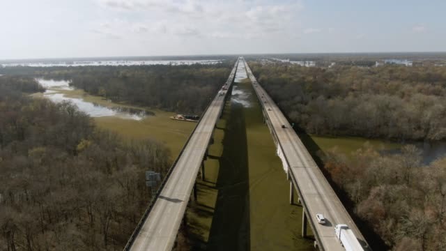 descending aerial drone shot of flying next to  breaux bridge (interstate 10) with salvinia floating on the atchafalaya river basin swamp surrounded by cypress tree forests in southern louisiana under a sunny but partly cloudy sky - elevated road stock videos & royalty-free footage