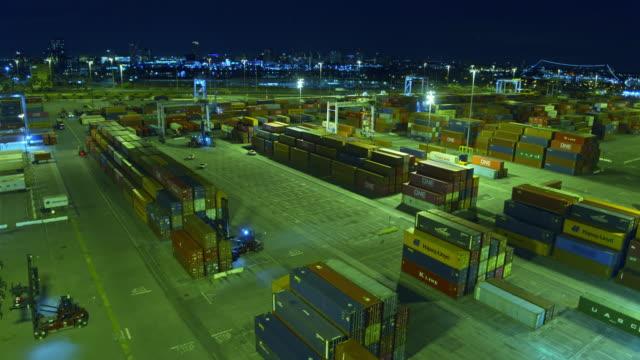 vídeos y material grabado en eventos de stock de descending aerial of port container terminal with long beach skyline lit up at night - puerto de los angeles