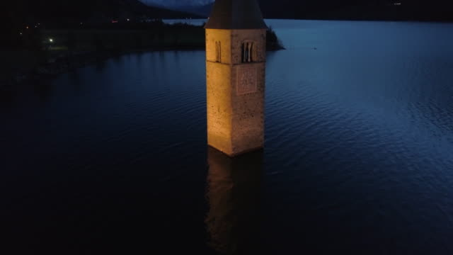 vídeos de stock e filmes b-roll de descending aerial: the brightly lit bell tower of lake reschen at night before dark hills and mountains - south tyrol, italy - brightly lit