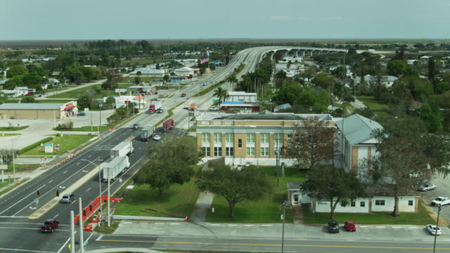 descending drone shot of county courthouse in moore haven, florida - straßenschild stock-videos und b-roll-filmmaterial