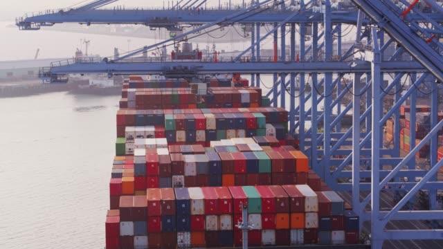 vidéos et rushes de descendant de drone coup de grues de déchargement à bord d'un cargo - port de commerce