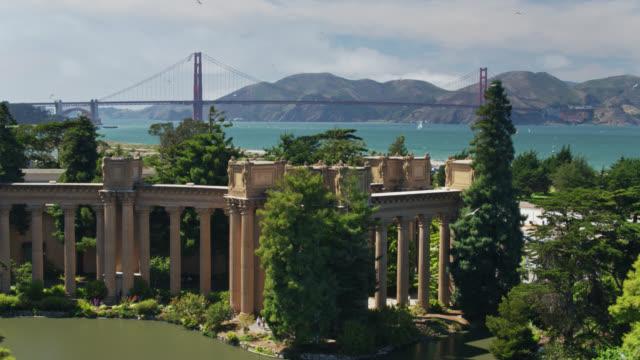 descending drone shot of golden gate bridge and academy of fine arts, san francisco - san francisco bay stock videos & royalty-free footage