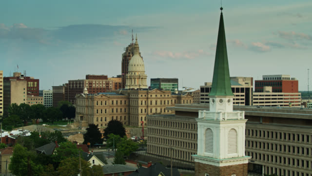 descending drone shot of michigan state capitol and van wagoner building past church steeple - lansing stock videos & royalty-free footage