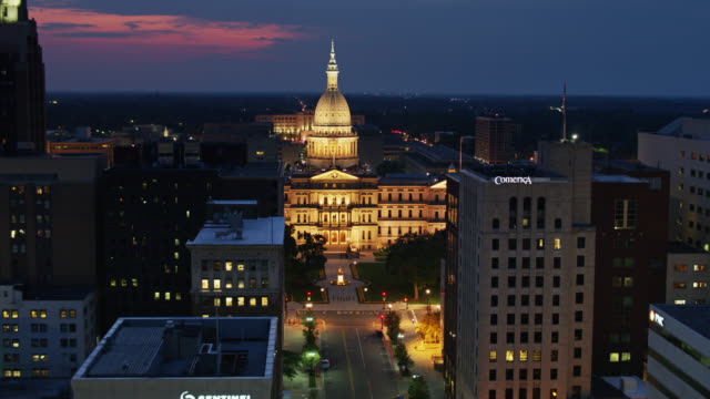 descending drone shot of michigan state capitol through downtown lansing buildings - lansing stock videos & royalty-free footage