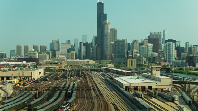 descending drone shot of rail yard and downtown chicago - willis tower stock videos & royalty-free footage