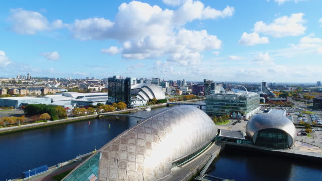 descending drone shot to the glasgow science centre, with city in background - museum stock videos & royalty-free footage